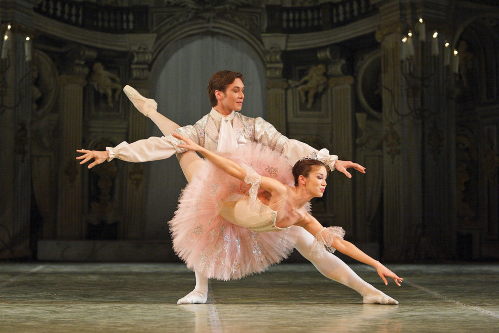 Male and female in elegant pink and white costumes performing the Sleeping Beauty ballet on stage