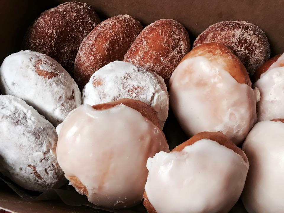 Delicious doughnuts layered. Iced, Powdered sugar, and glazed.