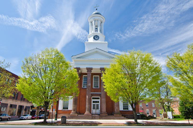 Stately historic Cumberland County Courthouse of red brick and white trim, fronted by green trees amidst blue skies