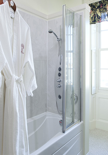 white terry cloth robe hanging next to glass enclosed tub and shower next to natural light coming through windo