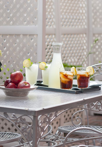 white wrought iron table with glass top and four chairs with bowl of red apples and tray with carafe of lemonade, two glasses of lemonade and two glasses of iced tea
