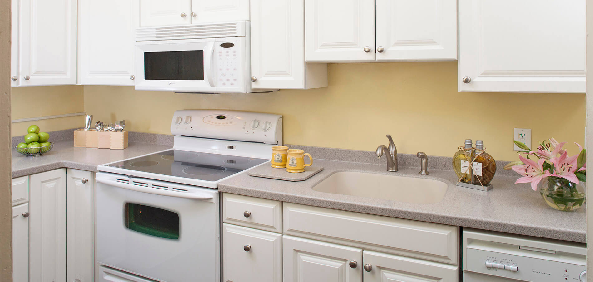 kitchen with white cabinets, soft gray granite countertops, white stove and microwave with soft yellow walls