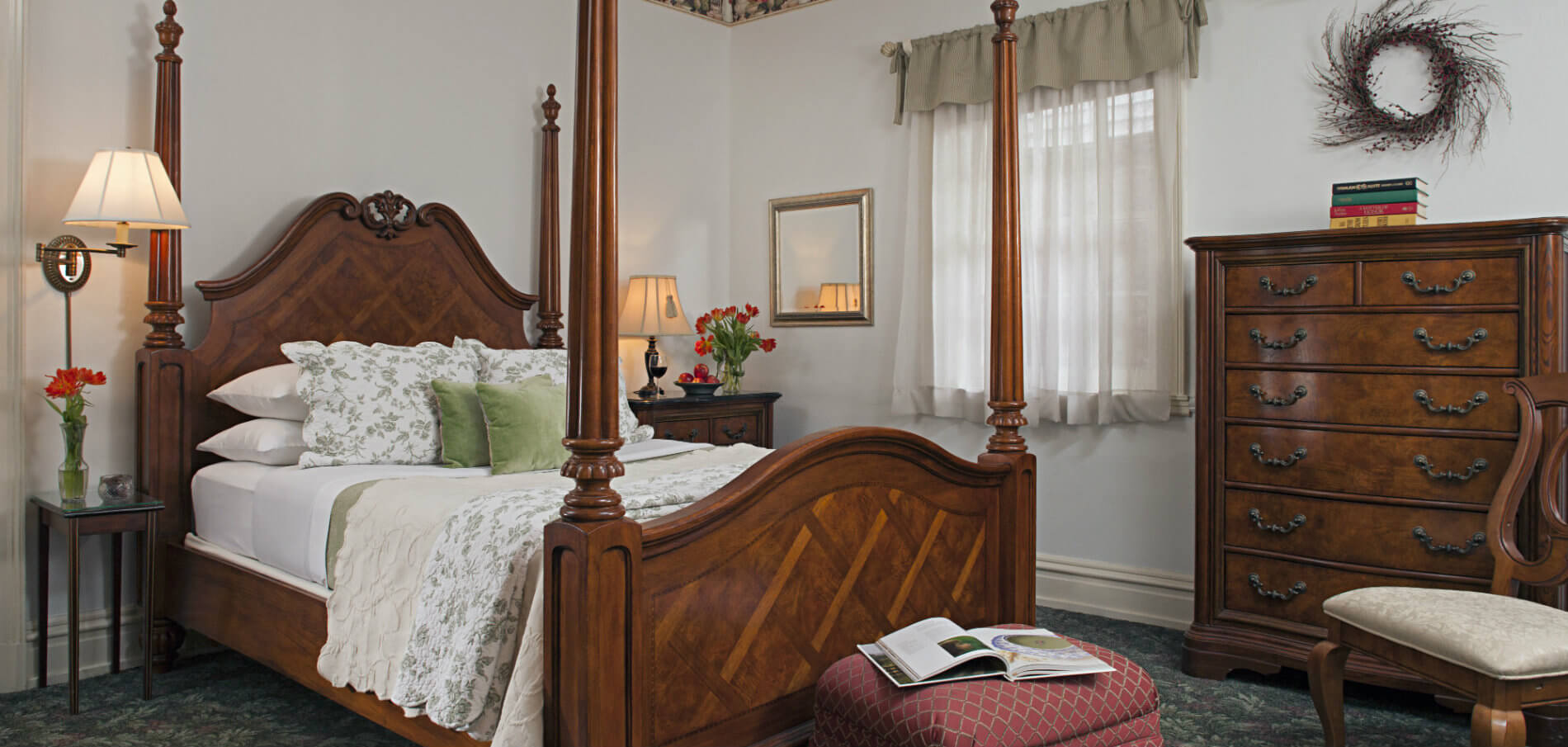 wood four poster bed with white and soft green linens, red flowers on nightstands on both sides, ottoman at foot of bed with open book, tall chest of drawers to right of bed