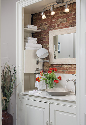 white cubby vanity with white marble suround, with bowl sink against original brick wall, with white trimmed mirror, overhead lighting, with chrome fixtures and crisp white towels