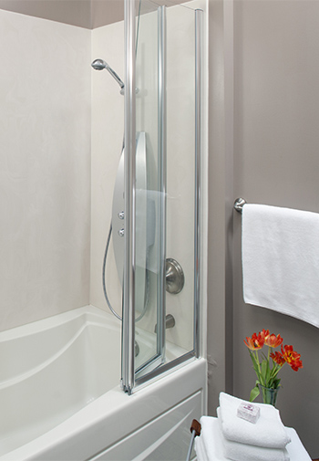 white suround tub with shower with soft gray wall with chrome fixtures and crisp white towels, and vibrant orange flowers in vase