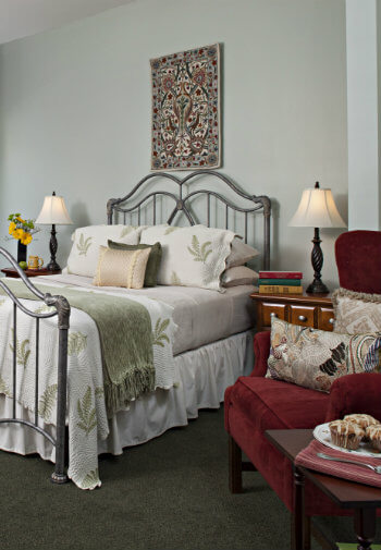 grey wrought iron bed with soft green linens against neutral green wall, maroon highback chair with tan pattern pillows and plate of iced muffins in foreground
