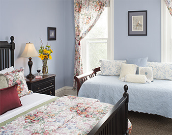 dark wood bed next to dark wood day bed in room with soft blue walls, natural light and blue and burgundy muted linens and window treatments, yellow flowers in vase on night stand