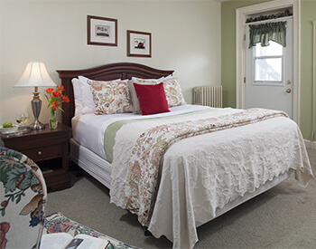 dark wook bed with white, baige linens with red and floral accents against white and beige walls