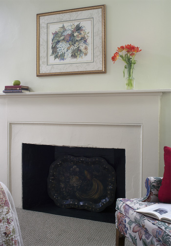 white antique mantel against neutral wall with glass vase with soft orange flowers and soft green and white floral print above