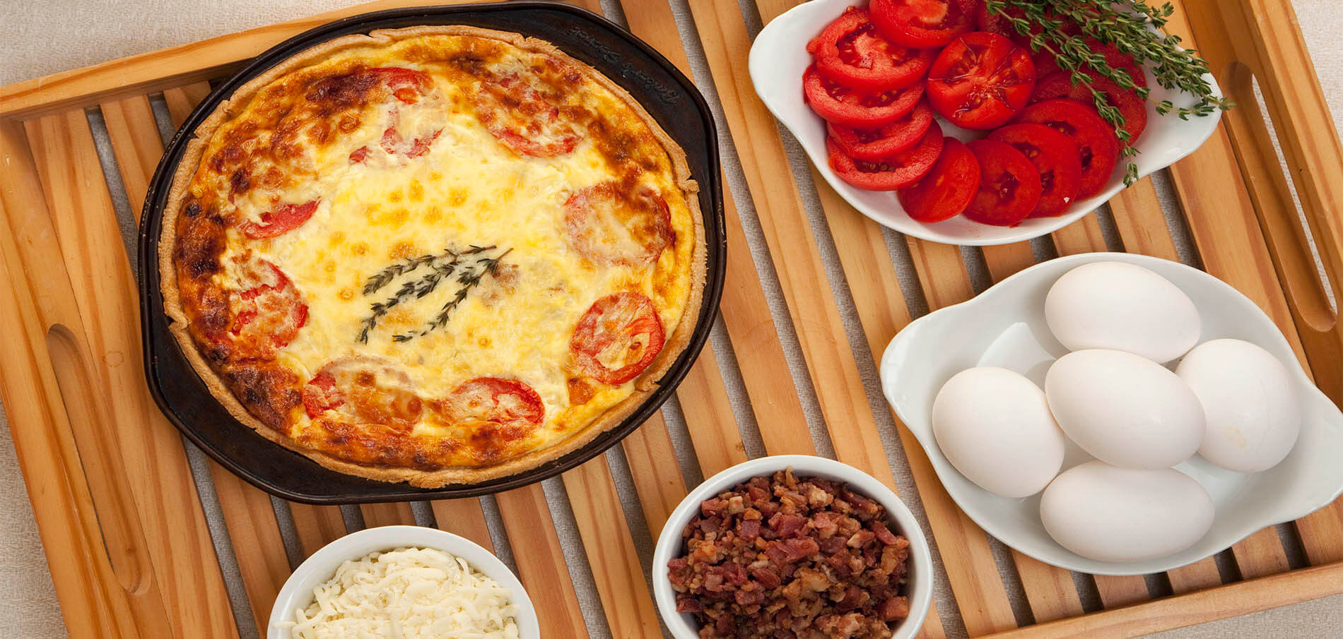 tomato and egg quiche in black cast iron dish surrounded by the ingredients in individual white bowls, including tomatoes, eggs, bacon and mozzarella cheese on light wooden slatted tray