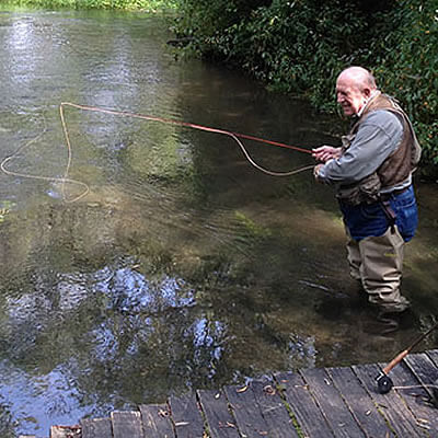 gentleman in tan waders in shallow stream after casting fly fishing rod