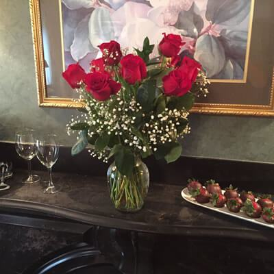 half a dozen red roses with baby's breath in glass vase on top of black iron mantel with two wine glasses and white serving dish with a dozen chocolalate dipped strawberries
