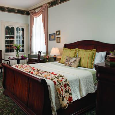 medium toned sleigh bed with white linens, gold accent pillows and traditional burgundy and green throw against white walls and large floor to ceiling windows with traditional gold window treatments and glass chandelier hanging overhead