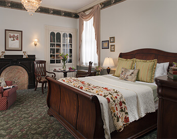 medium toned sleigh bed with white linens, gold accent pillows and traditoinal burguncy and green throw against white walls and large floor to ceiling windows with traditional gold window treatments and glass chandielier hanging overhead