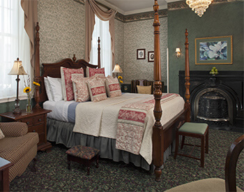 large wooden 4 poster bed with white and green linens and red and white accent pillows and throw with front of antique wrguth iron fireplace and surround with iron pot belly stove, bowl of green apples on top and paining of large magnolia above