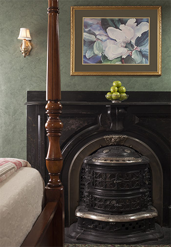 foot of wooden 4 poster bed in front of antique wrguth iron fireplace and surround with iron pot belly stove, bowl of green apples on top and paining of large magnolia above