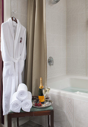 white terry cloth bathrobe hanging on hook next to whie tied tub, side table in front with rolled towells, silver platter with bottle of champage, two flutes and strawberries