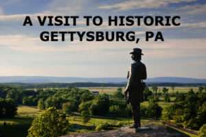 A PHOTO OF THE GENERAL WARREN STATUE ON TOP OF A HILL OVERLOOKING THE GETTYSBURG BATTLEFIELDS.