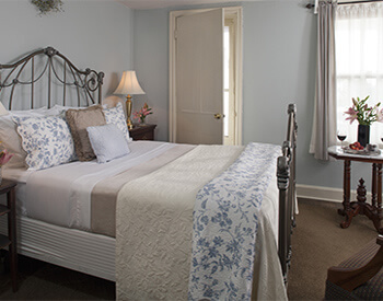 black wrought iron bed with soft cream, and beige linens in soft blue painted room