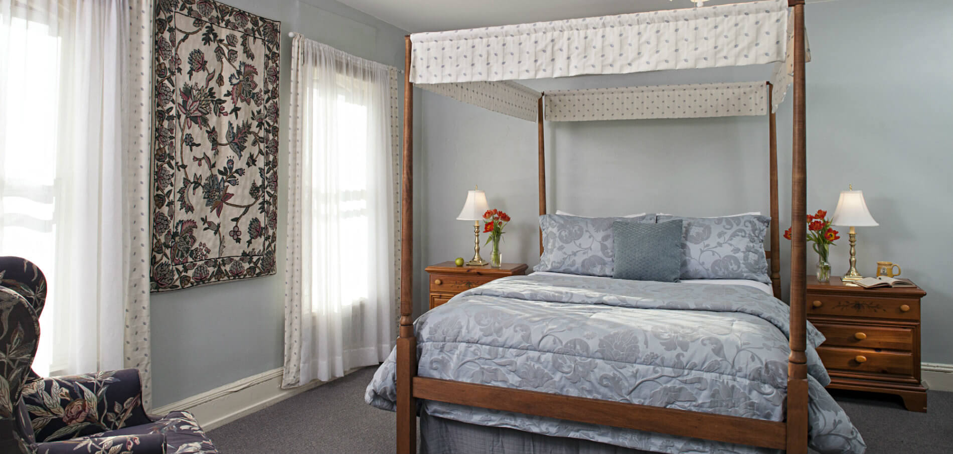 wood four poster bed with soft blue linens in bright room with decorative tapestry on wall between two windows
