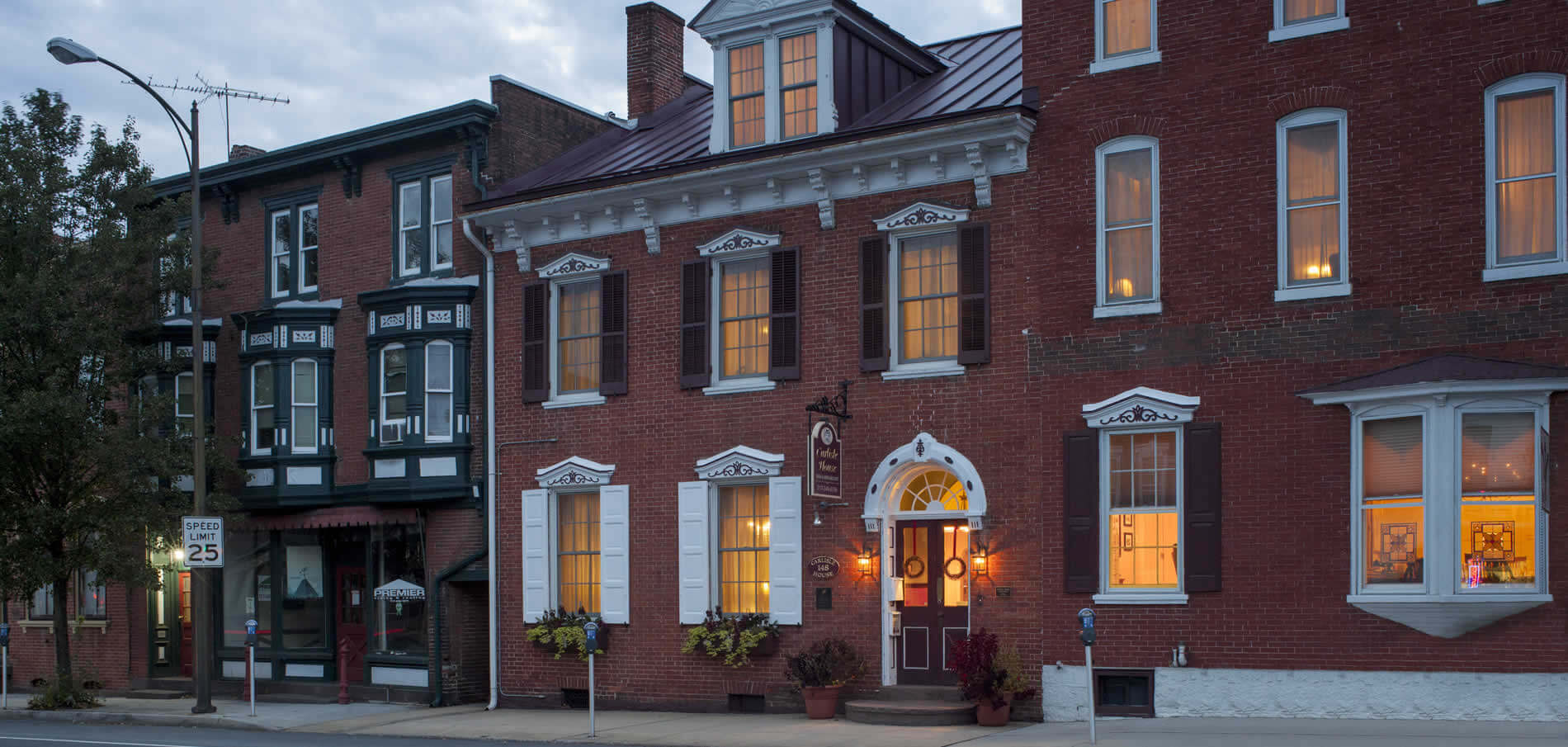 front brick facade of the inn in the early evening with lighted windows