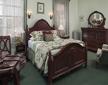 large mahogany bed with white, beige and floral linens, with red accent pillow in between floor to sealing windows with lace window treamentsb