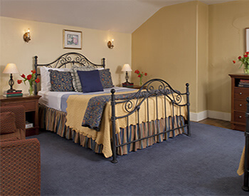 black wrought iron bed with soft yellow, blue and white linens on slate blue rug against cream colored walls