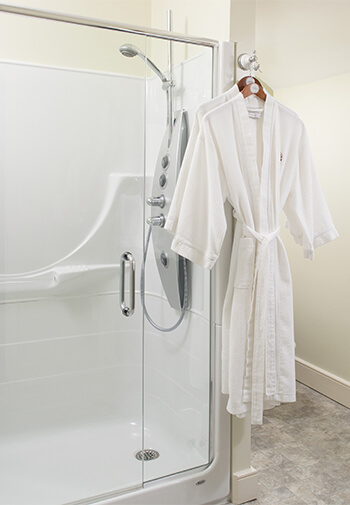 white terry cloth robe hanging next to glass encloses shower and bright white painted bathroom walls