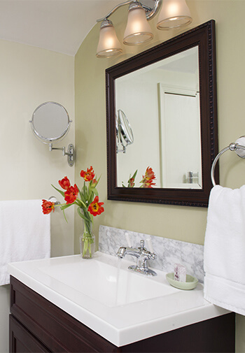 modern deep brown vanity with matching mirror above, white quartz counter with orange flowers in glass vase