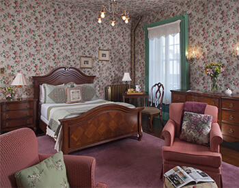 large medium toned wood bed, two rose club chairs against traditional rose wallpapered room