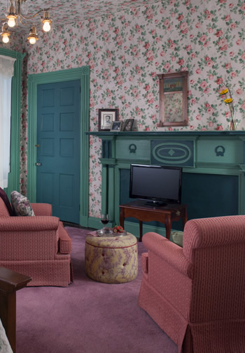 two rose club chairs facing soft green antique mantel and traditional rose wallpapered room