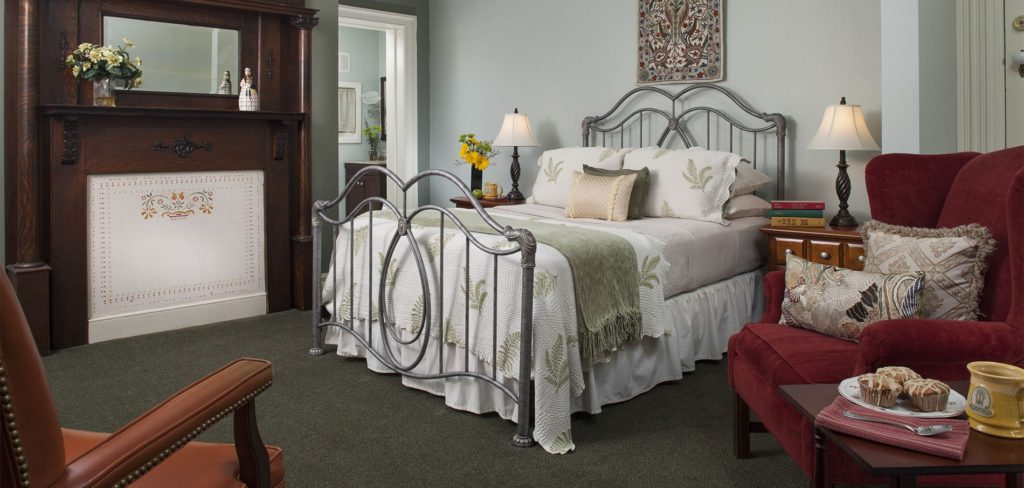 Seren and spacious carpeted guest room and bed topped with white and sage green bedding