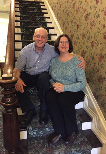 Tim and Carolyn sitting on the inside house stiars with stately wood banister and traditional red, green and beiege wallpaped entry