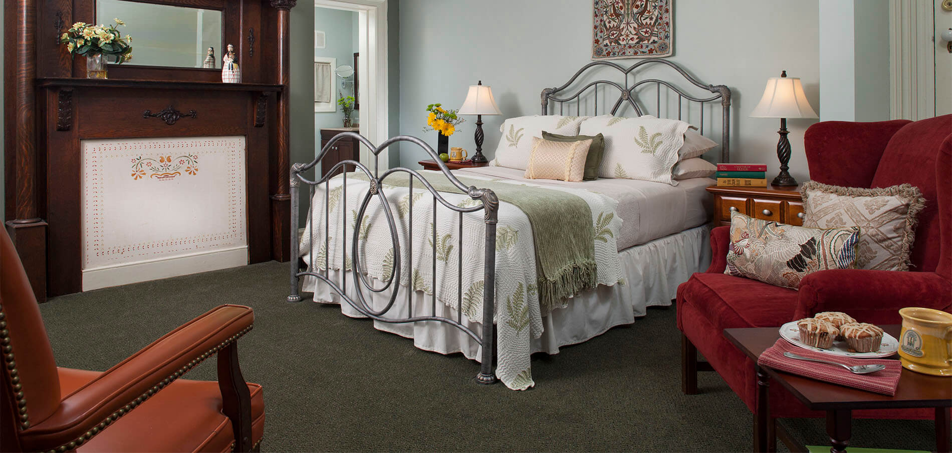 gray wrought iron bed with white and soft green linens next to antique wood and mirror mantel against neutral soft green walls